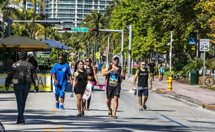 People enjoy the beautiful weather walking on Ocean Drive, as the of City of Miami Beach have implemented the Miami Beach Vacation Responsibly campaign, Tuesday March 2, 2021 in Miami Beach, Fla. Miami Beach officials are imposing an emergency 8 p.m.-6 a.m. curfew effective immediately, saying large, out-of-control spring break crowds crammed the beaches, trashed some restaurant properties and brawled in the streets. Tourists and hotel guests are being told to stay indoors during the curfew hours. (Pedro Portal/Miami Herald via AP)