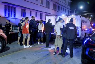 City of Miami Beach Police officers arrest several males on Ocean Drive and 10th Street as spring break has officially begun Saturday, Feb. 20, 2021 in Miami Beach, Fla. Miami Beach officials are imposing an emergency 8 p.m.-6 a.m. curfew effective immediately, saying large, out-of-control spring break crowds crammed the beaches, trashed some restaurant properties and brawled in the streets. Tourists and hotel guests are being told to stay indoors during the curfew hours. (Pedro Portal/Miami Herald via AP)