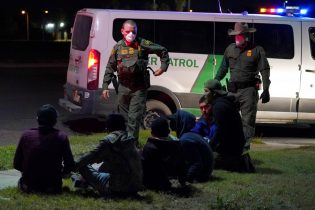 U.S. Customs and Border Protection agents take into custody people near the U.S.-Mexico border, Saturday, March 20, 2021, in Hidalgo, Texas. A surge of migrants on the Southwest border has the Biden administration on the defensive. The head of Homeland Security acknowledged the severity of the problem Tuesday but insisted it's under control and said he won't revive a Trump-era practice of immediately expelling teens and children. An official says U.S. authorities encountered nearly double the number children traveling alone across the Mexican border in one day this week than on an average day last month. (AP Photo/Julio Cortez)