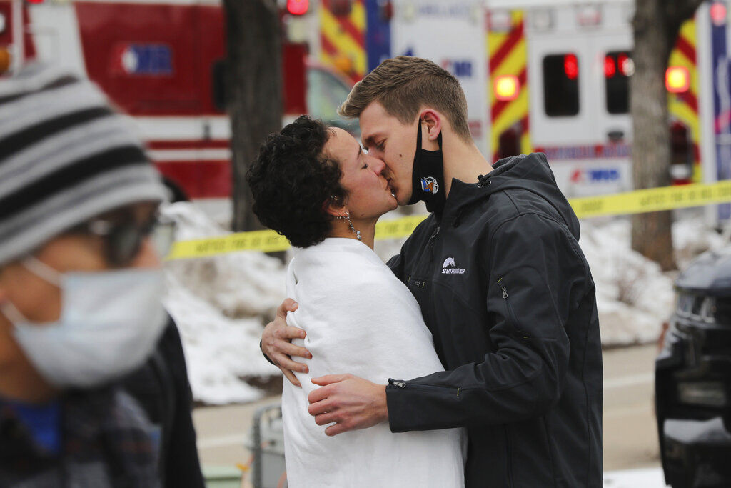 A man and woman kiss near the scene of a mass shooting in a King Soopers grocery store, Monday, March 22, 2021, in Boulder, Colo. (Hart Van Denberg/Colorado Public Radio viua AP)