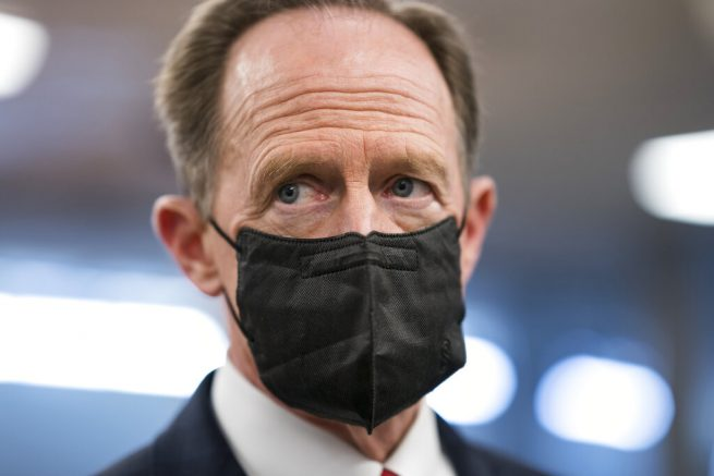 Sen. Pat Toomey, R-Pa., pauses for reporters as senators head to the chamber for a procedural vote on the nomination of Shalanda Young to be deputy director of the Office of Management and Budget, at the Capitol in Washington, Tuesday, March 23, 2021. (AP Photo/J. Scott Applewhite)