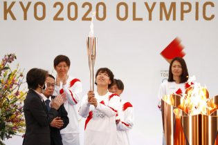 Tokyo 2020 Organizing Committee President Seiko Hashimoto, wearing a face mask, applauds Azusa Iwashimizu, a member of Nadeshiko Japan, Japan's women's national soccer team, carrying the torch during the Tokyo 2020 Olympic Torch Relay Grand Start in Naraha, Fukushima prefecture, northeastern Japan, Thursday, March 25, 2021. The torch relay for the postponed Tokyo Olympics began its 121-day journey across Japan on Thursday and is headed toward the opening ceremony in Tokyo on July 23. (Kim Kyung-Hoon/Pool Photo via AP)