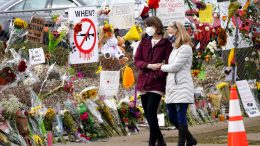 Mourners walk along the temporary fence put up around the parking lot of a King Soopers grocery store where a mass shooting took place earlier in the week Thursday, March 25, 2021, in Boulder, Colo. (AP Photo/David Zalubowski)