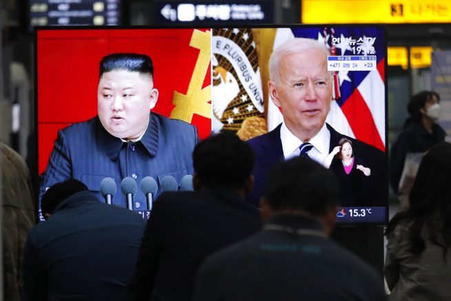 Commuters watch a TV showing a file image of North Korean leader Kim Jong Un and U.S. President Joe Biden during a news program at the Suseo Railway Station in Seoul South Korea