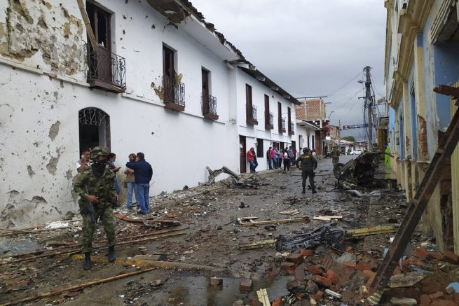 In this photo released by the press office of Corinto soldiers and civilians stand outside the City Hall of Corinto, Colombia, after the explosion of a car bomb on Friday, March 26, 2021. (Francy Otela, Corinto Press Office via AP)