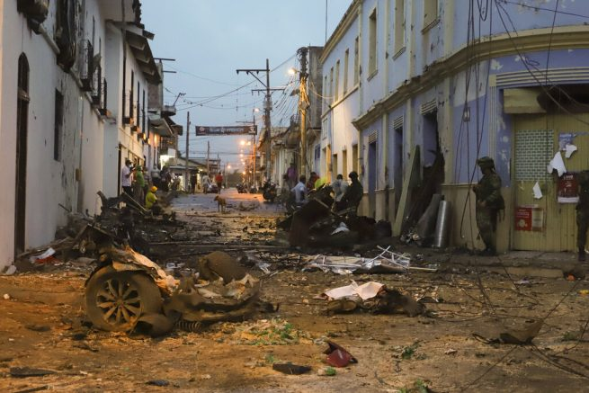 A soldier stand next to wreckage of a car bomb that exploded outside the City Hall of Corinto, Colombia, Friday, March 26, 2021. (AP Photo/Juan Bautista Diaz)