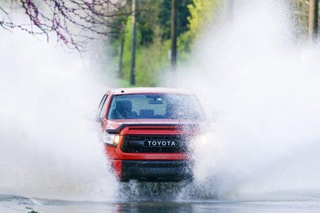 A truck drives through water on the road Sunday, March 28, 2021, in Nashville, Tenn. Heavy rain across Tennessee late Saturday and early Sunday flooded homes and roads as a line of severe storms crossed the state. (AP Photo/Mark Humphrey)