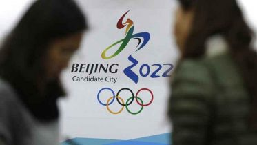 In this Nov. 4, 2014, file photo, journalists chat near the Beijing's bid for the 2022 Winter Olympics logo after attending a media briefing at the Beijing Olympics Headquarters in Beijing, China. A coalition of human-rights groups has met with the International Olympic Committee over calls to pull the 2022 Winter Olympics out of Beijing. (AP Photo / Andy Wong)
