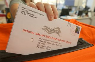 PROVO, UT - November 6: A employee at the Utah County Election office puts mail in ballots into a container to register the vote in the midterm elections on November 6, 2018 in Provo, Utah. Utah early voting has been the highest ever in Utah's midterm elections. One of the main proportions on the ballot in Utah is whether Utah will legalize medical marijuana. (Photo by George Frey/Getty Images)