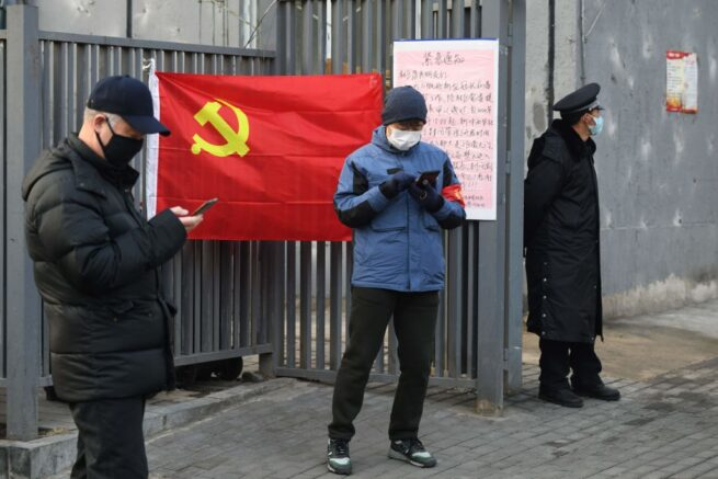 People wear protective face masks as they stand near a Communist Party flag at the entrance to a residential compound in Beijing on February 9, 2020. - The death toll from the novel coronavirus surged past 800 in mainland China on February 9, overtaking global fatalities in the 2002-03 SARS epidemic, even as the World Health Organization said the outbreak appeared to be stabilising. (Photo by GREG BAKER / AFP) (Photo by GREG BAKER/AFP via Getty Images)
