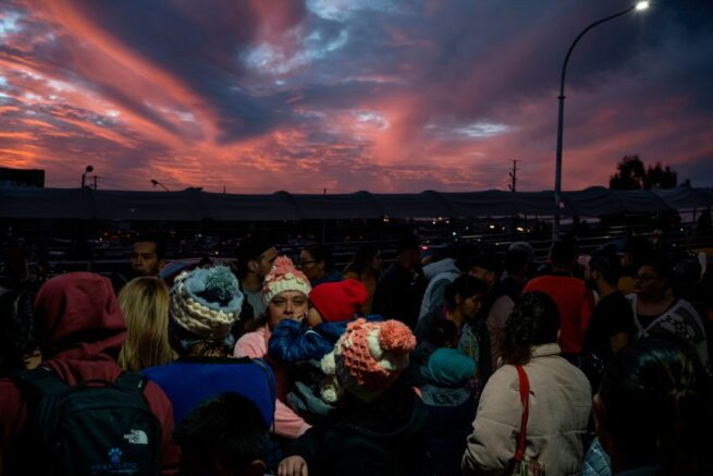 TOPSHOT - Migrants part of the Remain in Mexico policy wait at the entrance to the Paso del Norte International Bridge on February 28, 2020, in Ciudad Juárez. - Migrant Protection Protocols, better known as the Remain in Mexico Policy was blocked by the United States Court of Appeals for the Ninth Circuit, seeming to halt a policy which drastically reduced the amount of border crossings. However, the court later granted the Trump Administration a stay on the program, for fear of creating an influx on the southern border. (Photo by Paul Ratje / AFP) (Photo by PAUL RATJE/AFP via Getty Images)
