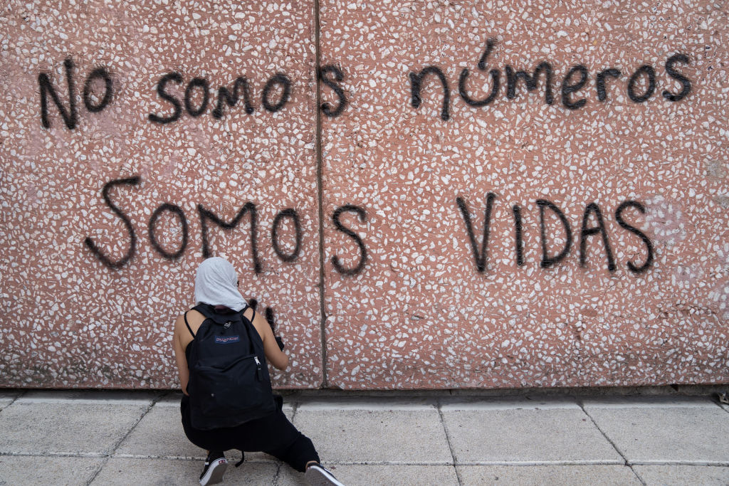 "MEXICO CITY, MEXICO - MARCH 08: A demonstrator paints a graffiti that reads ""we are not numbers, we are lives"" during a rally on International Women's Day on March 8, 2020 in Mexico City, Mexico. (Photo by Toya Sarno Jordan/Getty Images)"