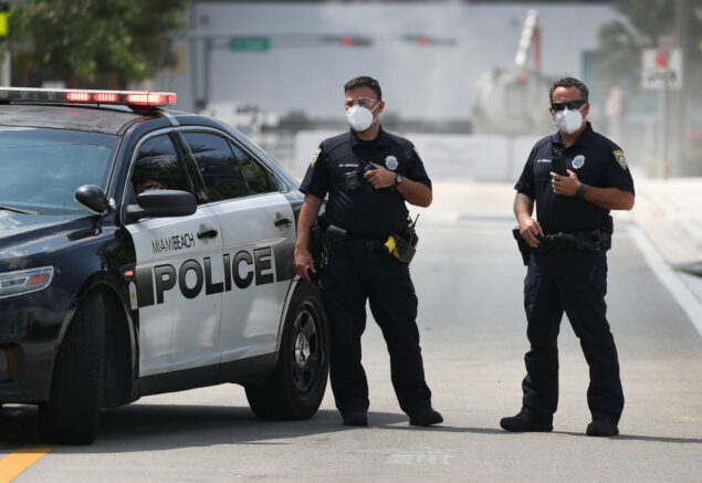 MIAMI BEACH, FLORIDA - APRIL 08: Miami Beach police officers wear protective masks as Florida Gov. Ron DeSantis along with other officials and politicians speak during a press conference at the Miami Beach Convention Center on April 08, 2020 in Miami Beach, Florida. Gov. DeSantis spoke about the U.S. Army Corp. of Engineers converting the convention center into a field hospital with 400 regular hospital beds and 50 ICU beds, with the ability to scale up to 1,000 beds if needed, as the region prepares for a possible surge of coronavirus patients.  (Photo by Joe Raedle/Getty Images)