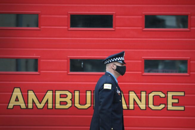 CHICAGO, ILLINOIS - APRIL 22: A police officer stands a post outside of a firehouse near the Taylor Funeral Home where a service was being held for Firefighter Edward Singleton, a 33 year veteran of the Chicago Fire Department, on April 22, 2020 in Chicago, Illinois. Singleton died last week from complications from COVID-19. In accordance with the social distancing restrictions imposed by the state, only 10 family members were allowed inside the funeral home for the service and firefighters and police officers joining in the procession were asked to remain inside of their cars during the service. (Photo by Scott Olson/Getty Images)