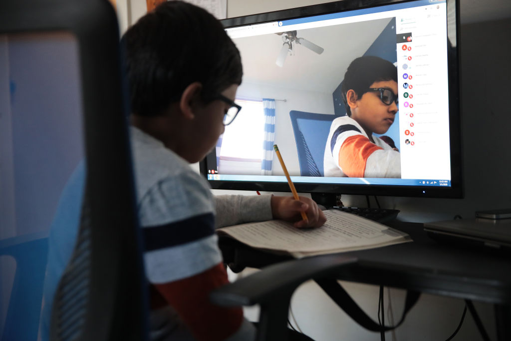 BARTLETT, ILLINOIS - MAY 01: Seven-year-old Hamza Haqqani, a 2nd grade student at Al-Huda Academy, uses a computer to participate in an E-learning class with his teacher and classmates while at his home on May 01, 2020 in Bartlett, Illinois. Al-Huda Academy, an Islam based private school that teaches pre-school through the 6th grade students, has had to adopt an E-learning program to finish the school year after all schools in the state were forced to cancel classes in an attempt to curtail the spread of the COVID-19 pandemic. (Photo by Scott Olson/Getty Images)