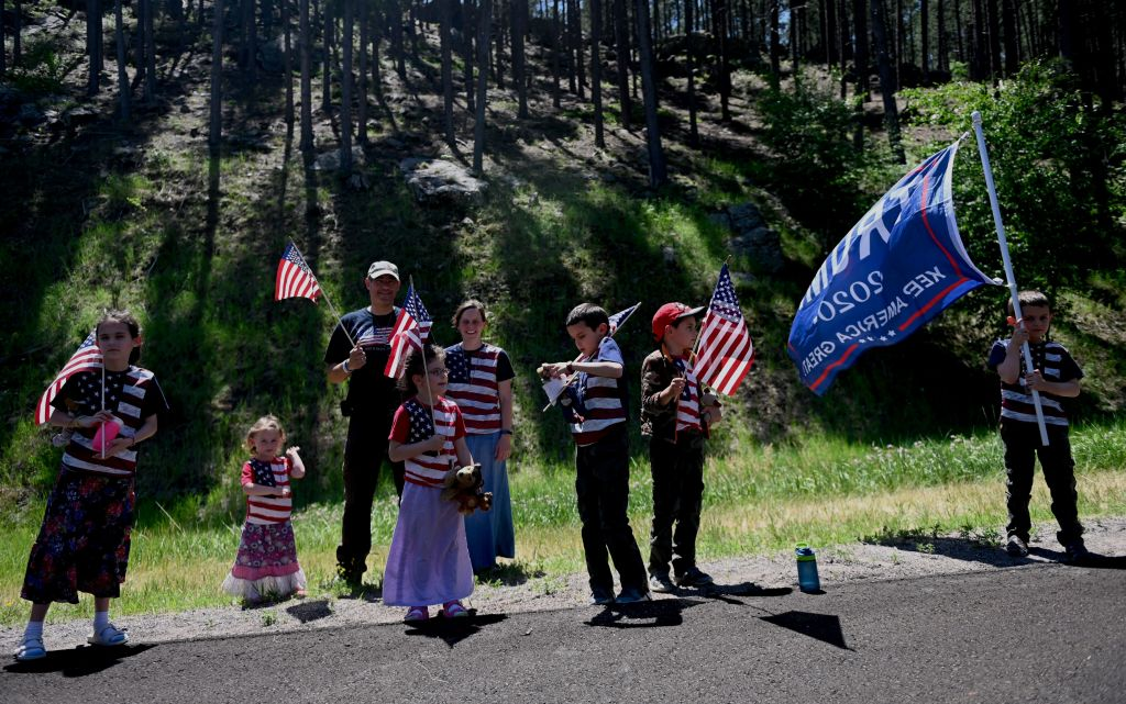 Supporters of US President Donald Trump wave flags on a road in Keystone, South Dakota, on July 3, 2020, before a fireworks celebration for the Fourth of July holiday at Mount Rushmore National Monument and the visit of US President Donald Trump. (Photo by Andrew Caballero-Reynolds / AFP) (Photo by ANDREW CABALLERO-REYNOLDS/AFP via Getty Images)
