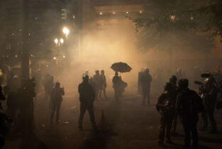 Protesters are surrounded by tear gas near the Mark O. Hatfield federal courthouse in downtown Portland as protesters take part in a rally against police brutality in Portland, Oregon late on July 24, 2020. - Police fired teargas and fought running battles with protesters in Portland in the latest night of demonstrations against police brutality and the deployment of federal troops to US cities. (Photo by Kathryn ELSESSER / AFP) (Photo by KATHRYN ELSESSER/AFP via Getty Images)