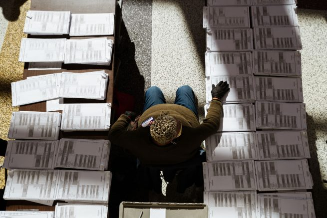 LOUISVILLE, KY - NOVEMBER 03: An election official sits between stacks of blank ballots in the polling area in the KFC YUM! Center on November 3, 2020 in Louisville, Kentucky. After a record-breaking early voting turnout, Americans head to the polls on the last day to cast their vote for incumbent U.S. President Donald Trump or Democratic nominee Joe Biden in the 2020 presidential election. (Photo by Jon Cherry/Getty Images)