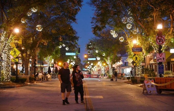 Two people walk down the main shopping and dining street in Burbank, California, currently closed to vehicular traffic to allow restaurants to serve food outside during the coronavirus panademic, November 23, 2020. - Starting November 24 Los Angeles County will suspend outdoor dining for restaurants in hopes of slowing an unprecedented surge in Covid-19 cases. The measure has sparked a backlash from eateries and some county officials, who worry about the devastating economic toll. Los Angeles County recorded its highest one-day total for COVID-19 cases on November 23 since the pandemic began. (Photo by Robyn Beck / AFP) (Photo by ROBYN BECK/AFP via Getty Images)