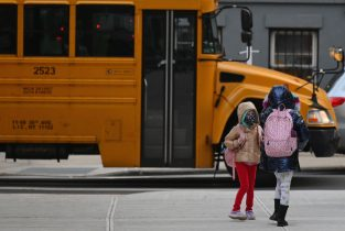 Children arrive for class on the first day of school reopening on December 7, 2020 in the Brooklyn borough of New York City. - The novel coronavirus has killed at least 1,535,987 people since the outbreak emerged in China last December, according to a tally from official sources compiled by AFP at 1100 GMT on Monday. The US is the worst-affected country with 282,324 deaths. (Photo by Angela Weiss / AFP) (Photo by ANGELA WEISS/AFP via Getty Images)