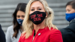 """US Representative Marjorie Taylor Greene, Republican of Georgia, holds up a """"Stop the Steal"""" mask while speaking with fellow first-term Republican members of Congress on the steps of the US Capitol in Washington, DC, January 4, 2021. - Donald Trump and Joe Biden head to Georgia on Monday to rally their party faithful ahead of twin runoffs that will decide who controls the US Senate, one day after the release of a bombshell recording of the outgoing president that rocked Washington.If Democratic challengers defeat the Republican incumbents in both races Tuesday, the split in the upper chamber of Congress will be 50-50, meaning incoming Vice President Kamala Harris will have the deciding vote. (Photo by SAUL LOEB / AFP) (Photo by SAUL LOEB/AFP via Getty Images)"""