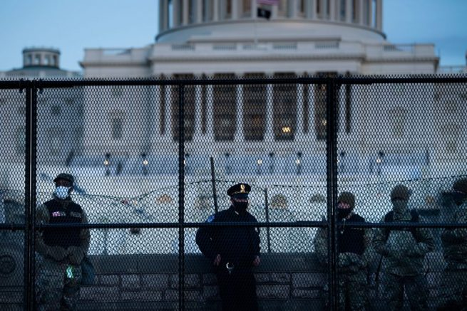 TOPSHOT - A Capitol Police officer stands with members of the National Guard behind a crowd control fence surrounding Capitol Hill a day after a pro-Trump mob broke into the US Capitol on January 7, 2021, in Washington, DC. (Photo by Brendan Smialowski / AFP) (Photo by BRENDAN SMIALOWSKI/AFP via Getty Images)