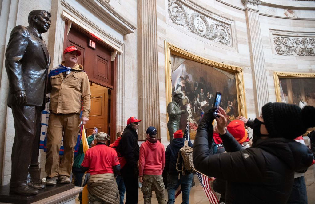 Supporters of US President Donald Trump pose with statues inside the Rotunda after breaching the US Capitol in Washington, DC, January 6, 2021. - The demonstrators breeched security and entered the Capitol as Congress debated the 2020 presidential election Electoral Vote Certification. (Photo by SAUL LOEB / AFP) (Photo by SAUL LOEB/AFP via Getty Images)