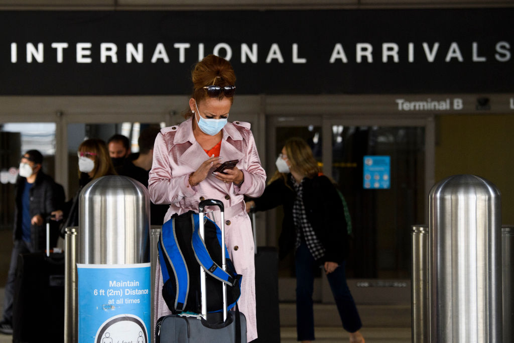 A traveler wears a face mask while checking their phone on the arrivals level outside the Tom Bradley International Terminal (TBIT) at Los Angeles International Airport (LAX) amid increased Covid-19 travel restrictions on January 25, 2021 in Los Angeles, California. - President Joe Biden will re-impose a Covid-19 travel ban on most non-US citizens who have been in Britain, Brazil, Ireland and much of Europe, a White House official said, as the new administration ramps up its pandemic response. (Photo by Patrick T. FALLON / AFP) (Photo by PATRICK T. FALLON/AFP via Getty Images)