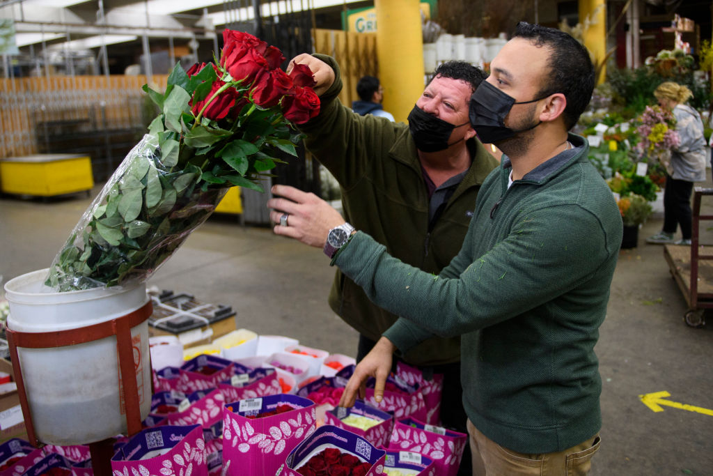Merchant Jesus Barajas (C) wears a face mask as he shows long stem roses for sale ahead of the Valentine's Day holiday at the Southern California Flower Market on February 12, 2021 in Los Angeles, California. - While some florists note an increased demand for socially distant gifts, the Covid-19 pandemic has impacted global supply chains and shut down most large events including weddings where flowers are popular. The Valentine's Day and Mother's Day holidays are historically the two busiest days of the year for floral businesses. (Photo by Patrick T. FALLON / AFP) (Photo by PATRICK T. FALLON/AFP via Getty Images)