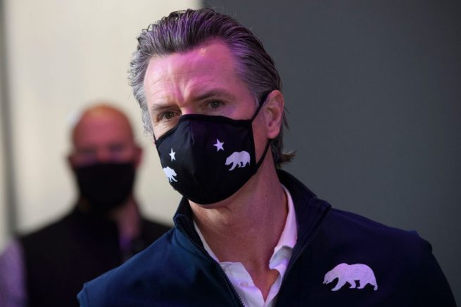 California Governor Gavin Newsom wears a face mask as he prepares to give a briefing after touring a Covid-19 vaccination site on February 22, 2021 in Long Beach, California. - US President Joe Biden will lead a remembrance ceremony Monday to mark the dark milestone of 500,000 American Covid-19 deaths, but plans for easing the lockdown in Britain and a surge in vaccinations worldwide prompted growing optimism. (Photo by Patrick T. FALLON / AFP) (Photo by PATRICK T. FALLON/AFP via Getty Images)