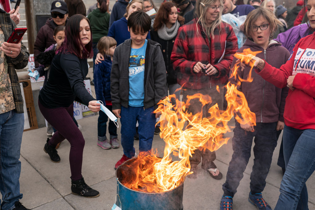 BOISE, ID - MARCH 06: A protester tosses a surgical mask into the fire during a mask burning event at the Idaho Statehouse on March 6, 2021 in Boise, Idaho. Citizens and politicians, including the Lieutenant Governor Janice McGeachin, gathered in at least 20 cities across the state to protest COVID-19 restrictions. (Photo by Nathan Howard/Getty Images)