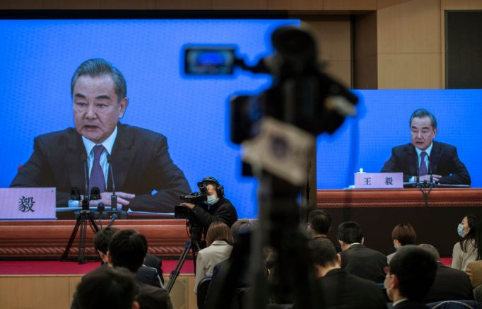 BEIJING, CHINA - MARCH 07: China's Foreign Minister Wang Yi, on screen, answers a question during a video news conference, held remotely as a precaution for COVID-19, as part of the National People's Congress on March 7, 2021 in Beijing, China.The annual political gatherings of the National Peoples Congress and the Chinese People's Political Consultative Conference, known as the Two Sessions, brings together Chinas leadership and lawmakers to set the blueprint for the coming year.  It is considered the most important event on the governments calendar and offers a rare glimpse at what President Xi Jinping and top officials see as priorities.  With the pandemic largely under control in China, discussions this year are expected to signal Beijings intentions around technology competition, control over Hong Kong, and strategic threats posed by Western countries including the United States. The political meetings, held at the Great Hall of the People at the edge of Tiananmen Square in central Beijing, can typically last for up to two weeks. (Photo by Kevin Frayer/Getty Images)