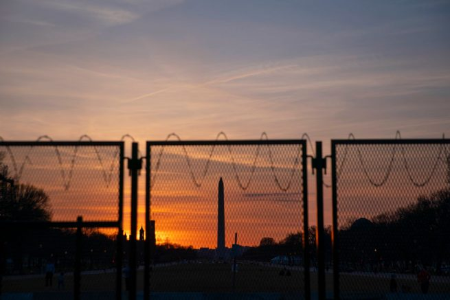 The Washington Monument is seen at sunset from behind a barbed wire fence perimeter that surrounds the U.S. Capitol on March 8, 2021 in Washington, DC. The House is scheduled to begin vote on the Senate's Covid-19 relief bill later this week. (Photo by Sarah Silbiger/Getty Images)