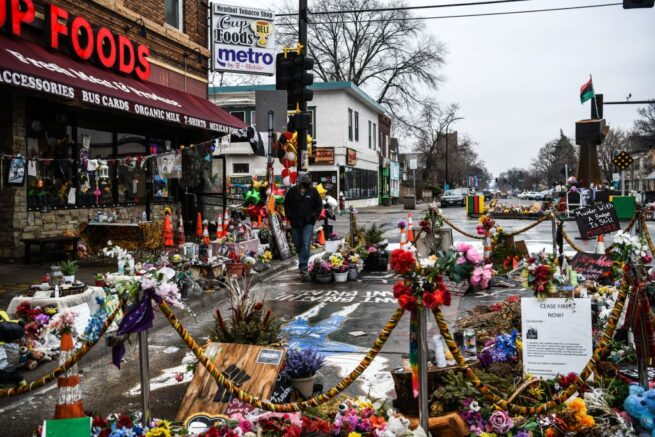 """A man walks in the makeshift memorial of George Floyd before the third day of jury selection begins in the trial of former Minneapolis Police officer Derek Chauvin who is accused of killing Floyd, in Minneapolis, Minnesota on March 10, 2021. - The first jurors were selected on March 9, 2021 in the high-profile trial of the white police officer accused of killing George Floyd, an African-American man whose death laid bare racial wounds in the United States and sparked """"Black Lives Matter"""" protests across the globe. Former Minneapolis Police Department officer Derek Chauvin is facing charges of second-degree murder and manslaughter in connection with Floyd's May 25 death, which was captured by bystanders on smartphone video. (Photo by CHANDAN KHANNA / AFP) (Photo by CHANDAN KHANNA/AFP via Getty Images)"""