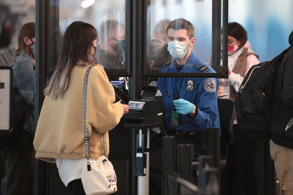 CHICAGO, ILLINOIS - OCTOBER 19: A Transportation Security Administration (TSA) agent screens an airline passenger at O'Hare International Airport on October 19, 2020 in Chicago, Illinois. Yesterday the TSA reported that it had screened over 1 million passengers, representing the highest number of passengers screened at TSA checkpoints since March 17, 2020. During the week ending October 18, TSA screened 6.1 million passengers nationwide, the highest total since the start of the COVID-19 pandemic. (Photo by Scott Olson/Getty Images)