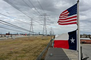 HOUSTON, TEXAS - FEBRUARY 21: The U.S. and Texas flags fly in front of high voltage transmission towers on February 21, 2021 in Houston, Texas. Millions of Texans lost power when winter storm Uri hit the state and knocked out coal, natural gas and nuclear plants that were unprepared for the freezing temperatures brought on by the storm. Wind turbines that provide an estimated 24 percent of energy to the state became inoperable when they froze. (Photo by Justin Sullivan/Getty Images)