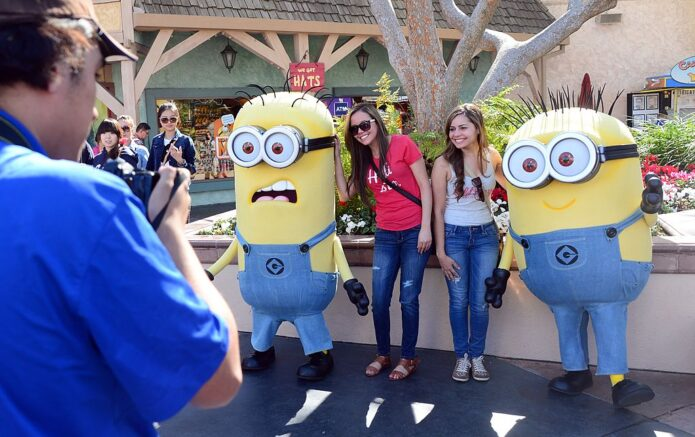 Girls pose with people dressed as Minions at Universal Studios where the Despicable Me Minion Mayhem attraction was still under construction on February 14, 2014 in Universal City, California. Building on the global success of the Despicable Me films and the enormous popularity of their mischievous little Minnions, entertainment giant Universal unveils on April 12 a new ride at its Hollywood theme park which lets visitors immerse themselves in the films yellow-tinged universe. AFP PHOTO/Frederic J. BROWN (Photo credit should read FREDERIC J. BROWN/AFP via Getty Images)