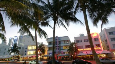 MIAMI BEACH, UNITED STATES: Renovated hotel buildings overlooking Ocean Drive are adorned by neon lights in the early evening 26 September 2006. The city of Miami Beach has a concentration of over 800 Art Deco buildings all within one square mile. The white-and pastel-colored stucco buildings originally built in the 1920's have in the past two decades been restored to their former splendor. Some of the characteristics of the Art Deco movement in Miami include over-all symmetry, ziggurat (stepped) rooflines, glass block, decorative sculptural panels, eyebrows, round porthole windows, terrazzo floors, curved edges and corners, elements in groups of three and neon lighting used in both exteriors as well as interior spaces. The chamber of commerce for the city reports that some 7,281,200 visitors came to South Beach in 2004. AFP PHOTO/Roberto Schmidt (Photo credit should read ROBERTO SCHMIDT/AFP via Getty Images)