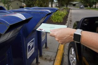 FILE - In this Tuesday, Aug. 18, 2020, file photo, a person drops applications for mail-in-ballots into a mailbox in Omaha, Neb. Data obtained by The Associated Press shows Postal Service districts across the nation are missing the agencys own standards for on-time delivery as millions of Americans prepare to vote by mail. (AP Photo/Nati Harnik, File) (Copyright 2020 The Associated Press. All rights reserved)