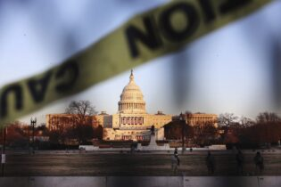 Caution tape flies Wednesday, Jan. 13, 2021 on a fence that was erected to reinforce security at the Capitol in Washington. (AP Photo/Shafkat Anowar)