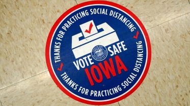 A Vote Safe Iowa sticker is seen on the floor during early voting for the general election, Tuesday, Oct. 20, 2020, in Adel, Iowa. (AP Photo/Charlie Neibergall)