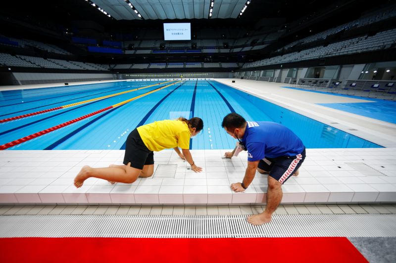 FILE PHOTO: Staff members work next to the swimming pool of the Tokyo Aquatics Centre, in Tokyo