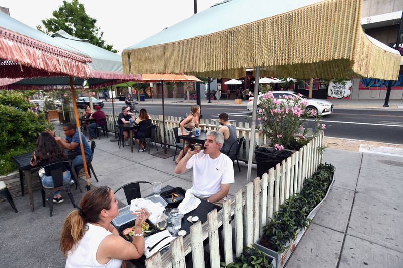FILE PHOTO: Cori Thune (L) and Phillip Thune dine outdoors at Park on Fremont as restaurants are opening for business on sidewalks as restrictions to prevent the spread of coronavirus disease (COVID-19) are eased in Las Vegas