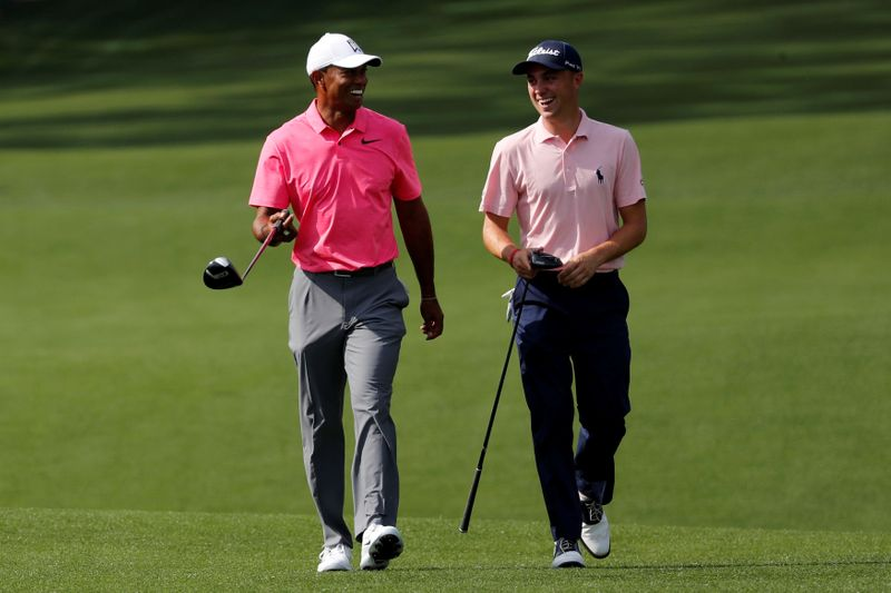 FILE PHOTO: Woods of the U.S. shares a laugh with compatriot Thomas during practice for the 2018 Masters golf tournament in Augusta