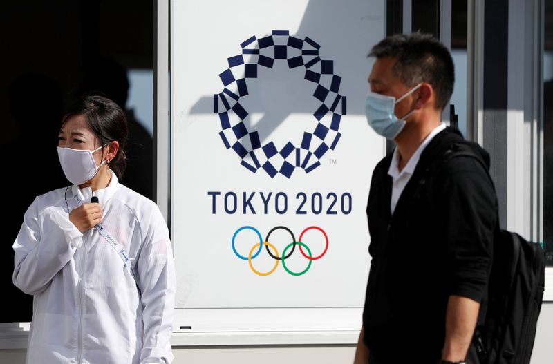 Officials acting the role of spectators perform a test session of screening measures for Olympic Games spectators in Tokyo