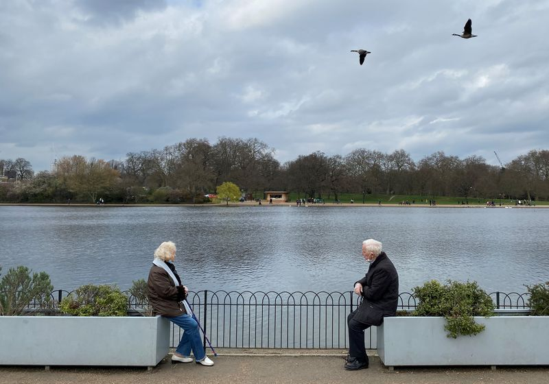 FILE PHOTO: Two people are seen socially distancing as they chat together in Hyde Park, London