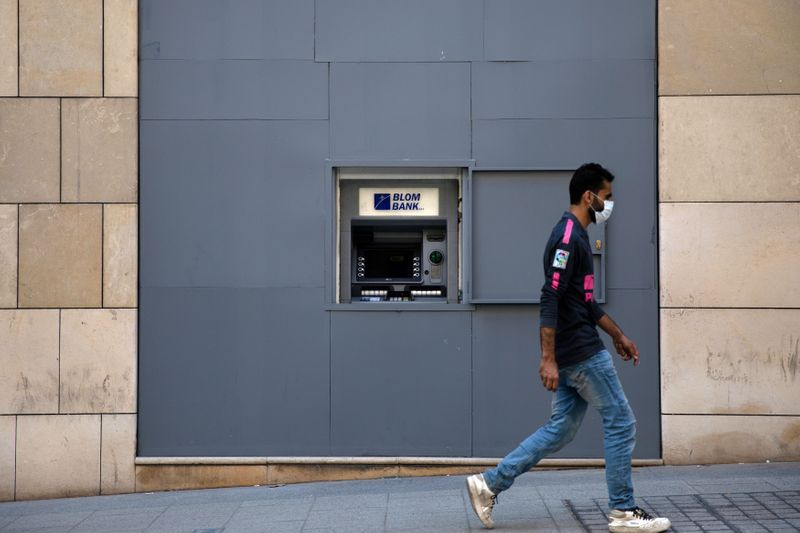 FILE PHOTO: A man wearing a face mask walks past a fortified ATM machine in Beirut