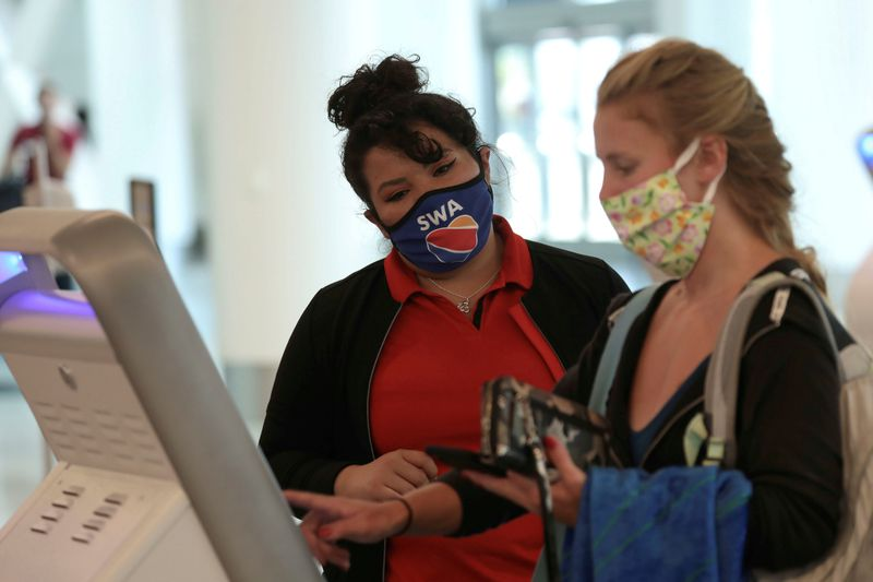 FILE PHOTO: A Southwest Airlines Co. employee wears a protective mask while assisting a passenger at Los Angeles International Airport (LAX) in Los Angeles