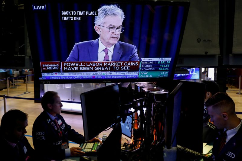 FILE PHOTO: Traders work as a screen shows Federal Reserve Chairman Jerome Powell's news conference after the U.S. Federal Reserve interest rates announcement on the floor of the  NYSE in New York