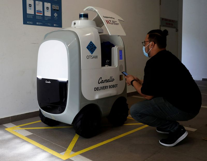 A customer collects his groceries from Camello, an autonomous grocery delivery robot, in Singapore
